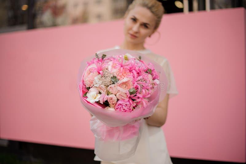 Flicka med buketten av rosa blommor royaltyfri fotografi