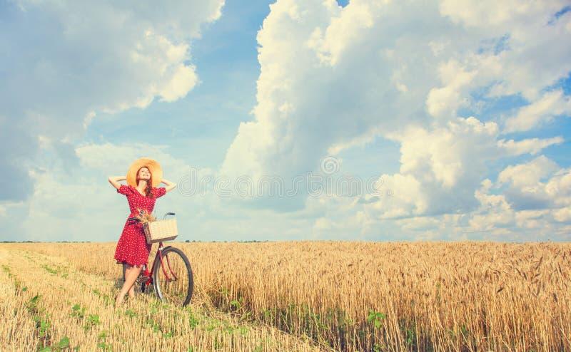 Flicka med cykeln på fält arkivbilder