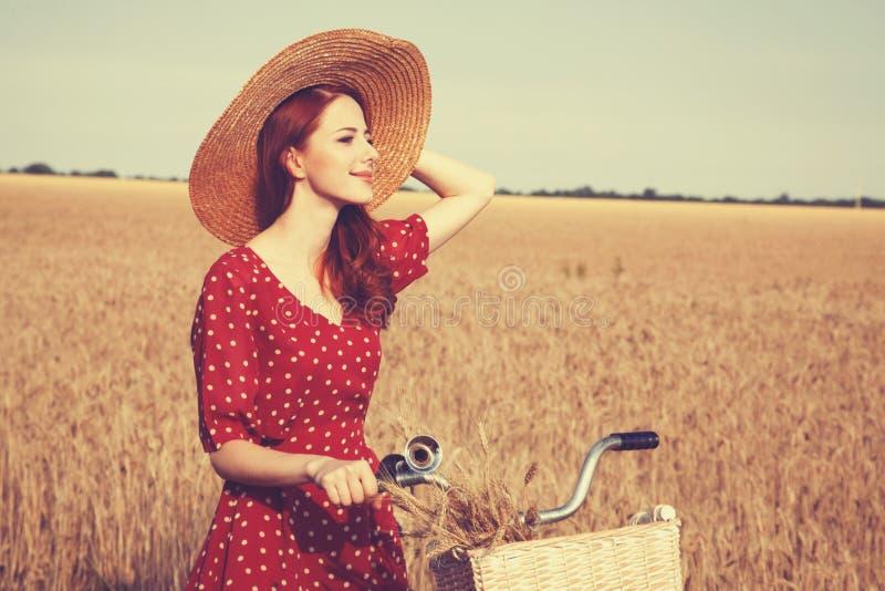 Flicka med cykeln på fält arkivfoto