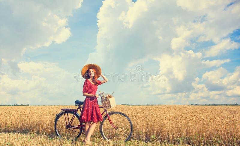 Flicka med cykeln på fält arkivfoton