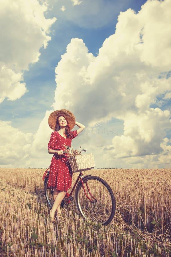 Flicka med cykeln på fält royaltyfria foton