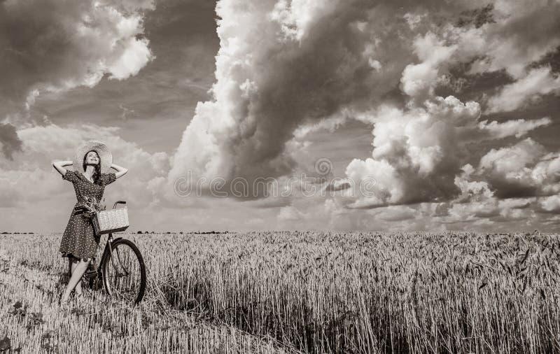 Flicka med cykeln på vetefält royaltyfria bilder