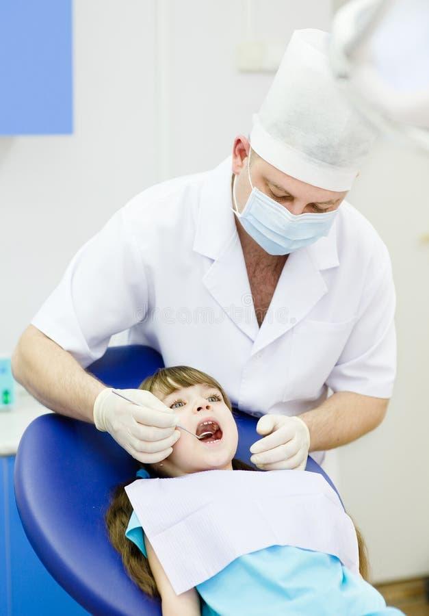 Flicka med den öppna munnen medan det som undersöks av tandläkaren royaltyfri foto