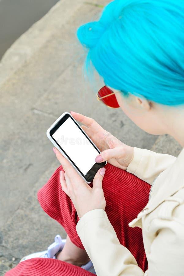 Flicka med den blåa hårbrukssmartphonen royaltyfri foto