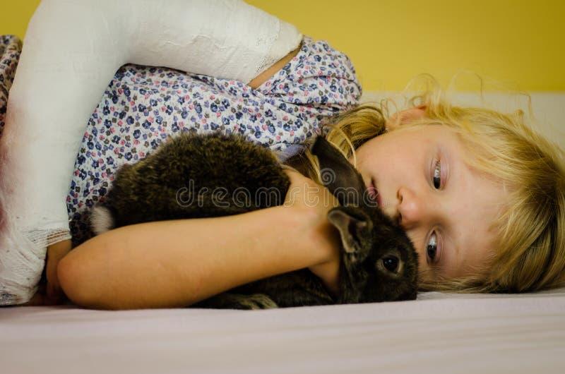 Flicka med den brutna handen och kanin arkivfoton