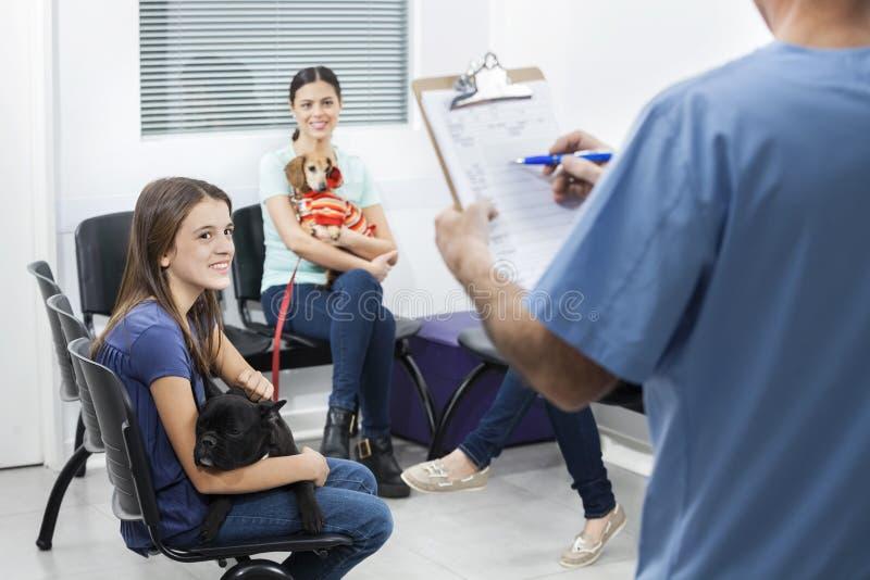 Flicka med den franska bulldoggen som ser sjuksköterskan Filling Form royaltyfria bilder