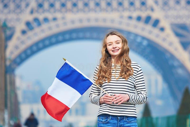 Flicka med den franska nationella tricolor flaggan nära Eiffeltorn arkivfoton