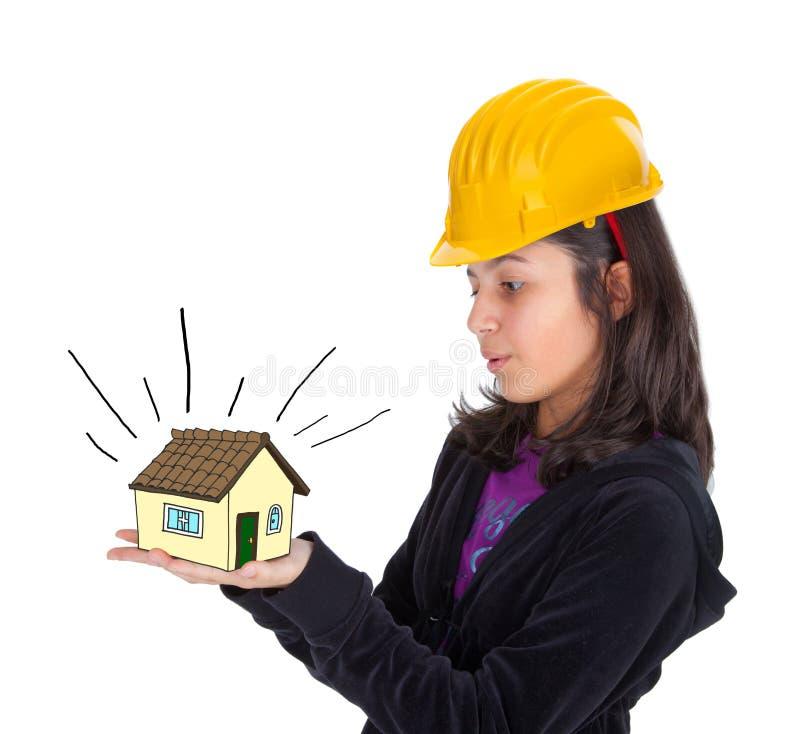 Flicka med den gula hjälmen och hus i hans händer royaltyfria foton