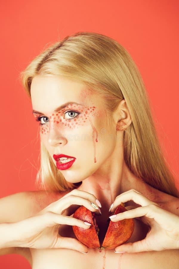 Flicka med den idérika trendiga makeuphållgranatäpplet, vitamin royaltyfri foto