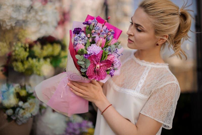 Flicka med den mycket gulliga buketten i rosa papper arkivbild