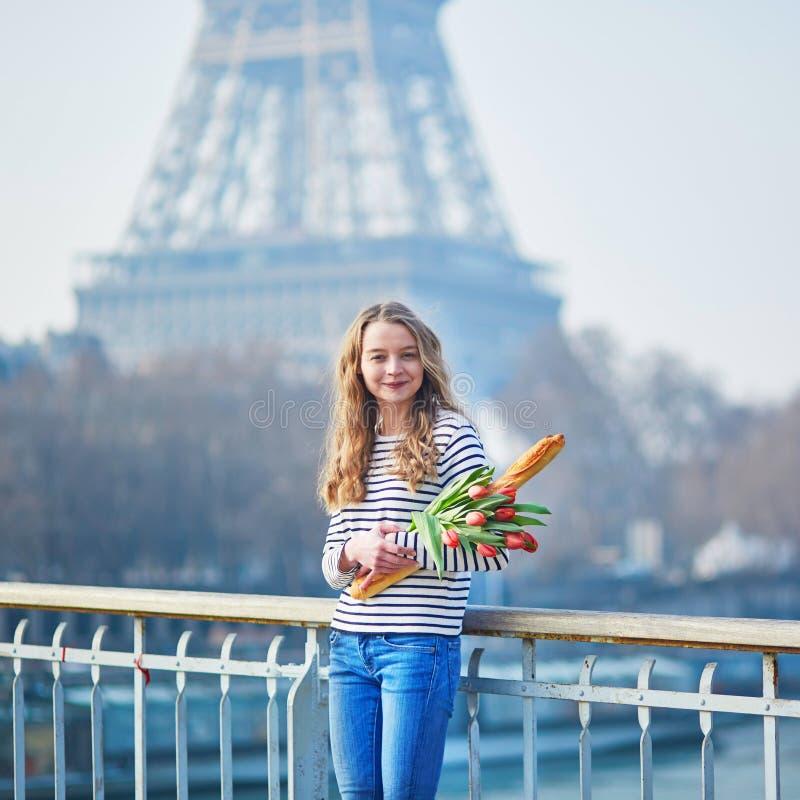 Flicka med den nya smakliga traditionella franskbrödbagetten och tulpan nära Eiffeltorn arkivbilder