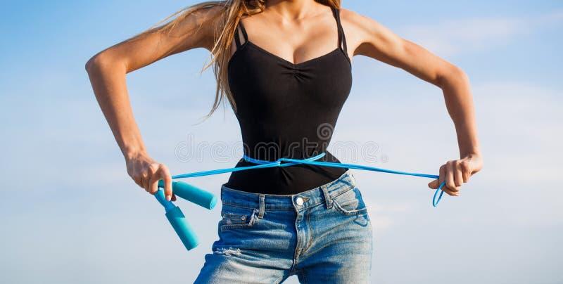 Flicka med den perfekta midjan med ett hopprep i h?nder F?rdig konditionflicka som m?ter hennes midja med m?ttbandet athirst royaltyfri bild