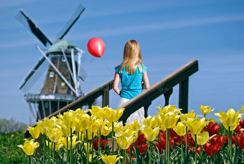 Flicka med den röda ballongen och väderkvarnen royaltyfria bilder