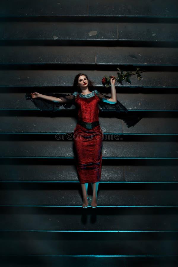 Flicka med den röda rosen som ligger på trappan på natten royaltyfri fotografi