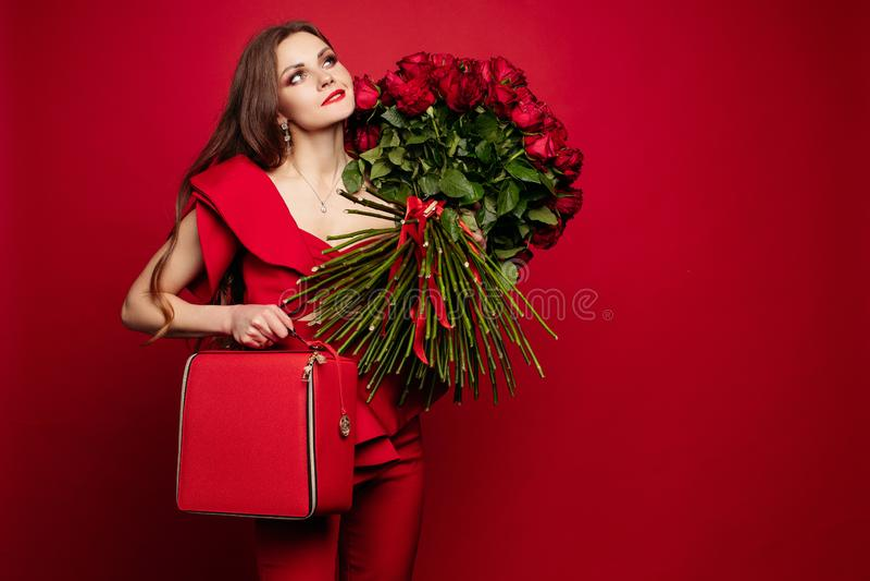 Flicka med den stora buketten av röda rosor på att drömma för skuldra fotografering för bildbyråer