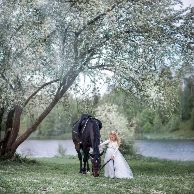Flicka med den svarta hästen i blomningträdgård arkivfoto