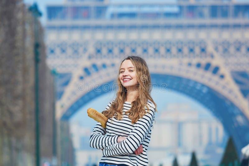 Flicka med den traditionella franska bagetten nära Eiffeltorn royaltyfri foto