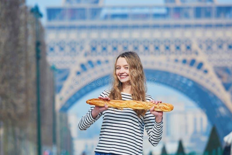 Flicka med den traditionella franska bagetten nära Eiffeltorn fotografering för bildbyråer