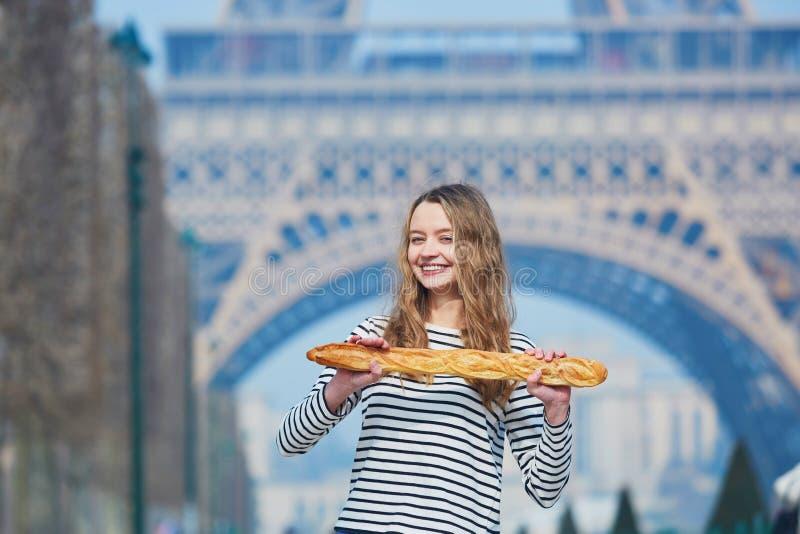 Flicka med den traditionella franska bagetten nära Eiffeltorn royaltyfri fotografi