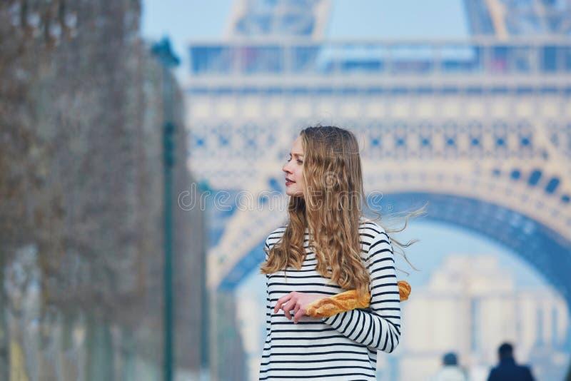 Flicka med den traditionella franska bagetten nära Eiffeltorn royaltyfria bilder