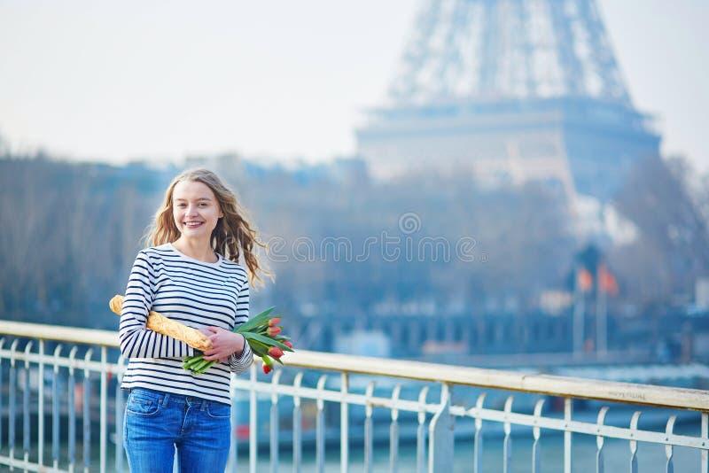Flicka med den traditionella franska bagetten och tulpan royaltyfria bilder