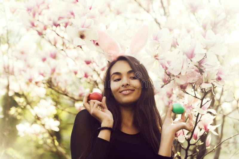 Flicka med det easter ägget, i kaninöron, magnolia royaltyfria bilder