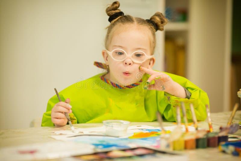 Flicka med Down Syndrome attraktionmålarfärger royaltyfria bilder
