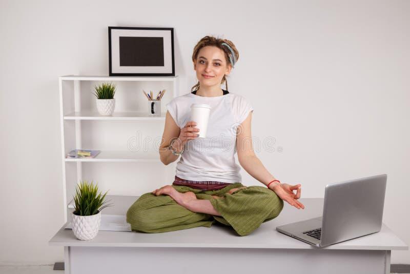 Flicka med dreadlocks som g?r yoga under att arbeta p? b?rbara datorn arkivfoton
