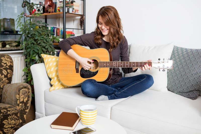 Flicka med en akustisk gitarr royaltyfria bilder