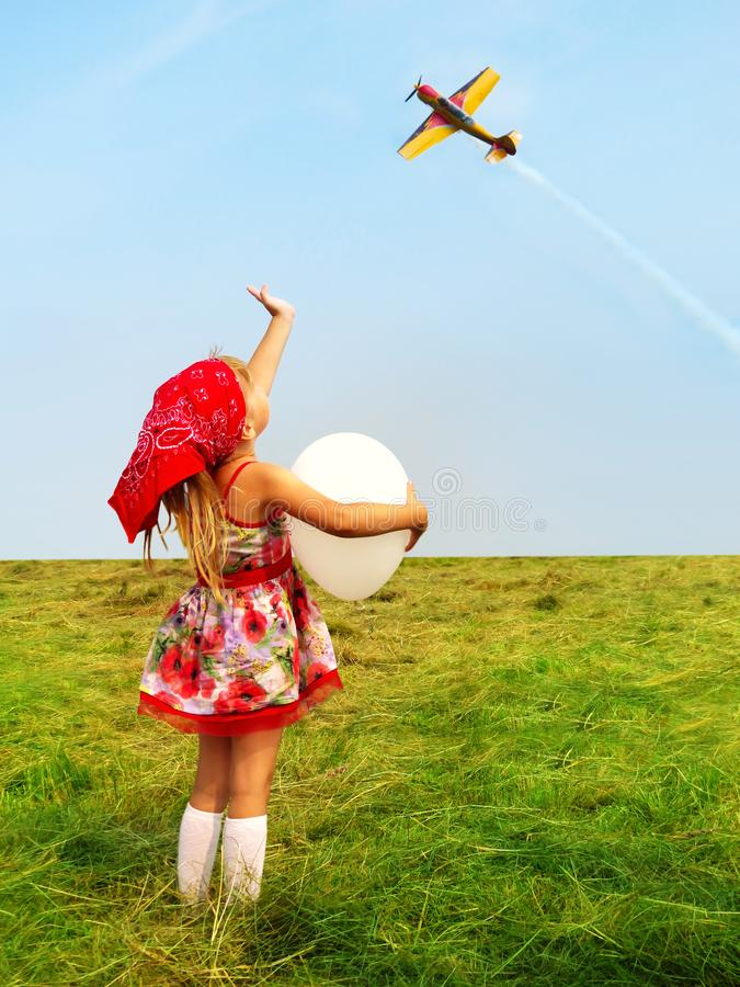 Flicka med en ballong som vinkar ett handflygflygplan royaltyfria bilder