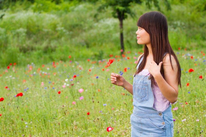 Flicka med en blommaväntan i vallmofält arkivfoto