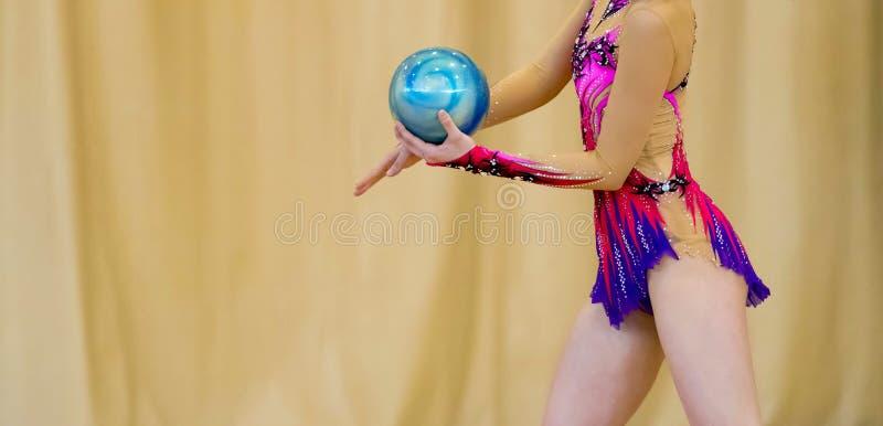 Flicka med en boll på en yrkesmässig gymnast Böjlighet i acrob royaltyfri bild