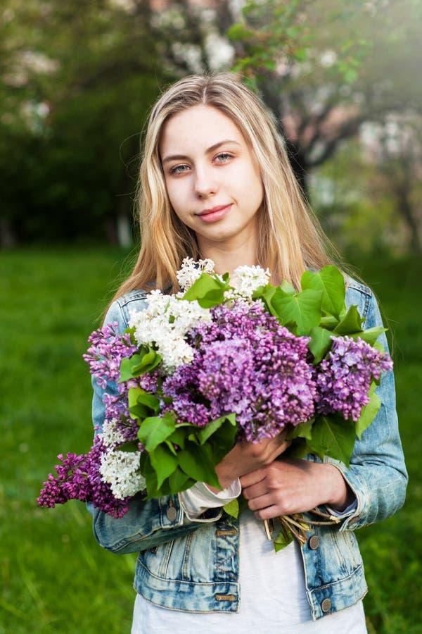 Flicka med en bukett av lilor arkivfoton