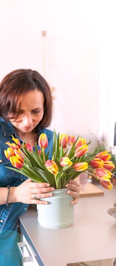 Flicka med en bukett av nya tulpan i rummet En gåva för en förälskad kvinna och födelsedagdagbegrepp lycklig kvinna royaltyfria foton