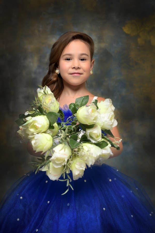 Flicka med en bukett av rosor i händer arkivfoton