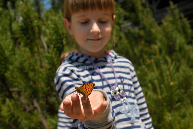 Flicka med en fjäril royaltyfria foton