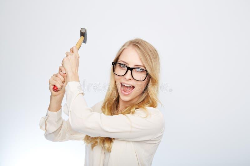 Flicka med en hammare och nerdexponeringsglas Isolerat på royaltyfria bilder
