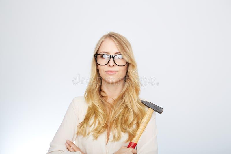 Flicka med en hammare och nerdexponeringsglas Isolerat på royaltyfri fotografi