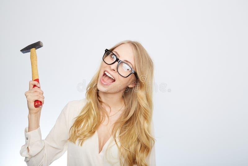 Flicka med en hammare och nerdexponeringsglas Isolerat på royaltyfria foton
