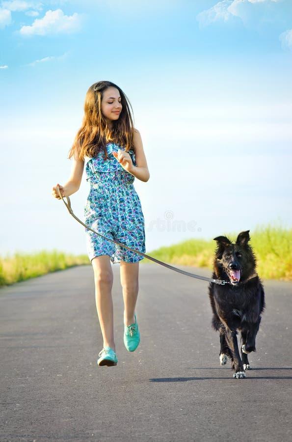 Flicka med en hund för en gå royaltyfria foton