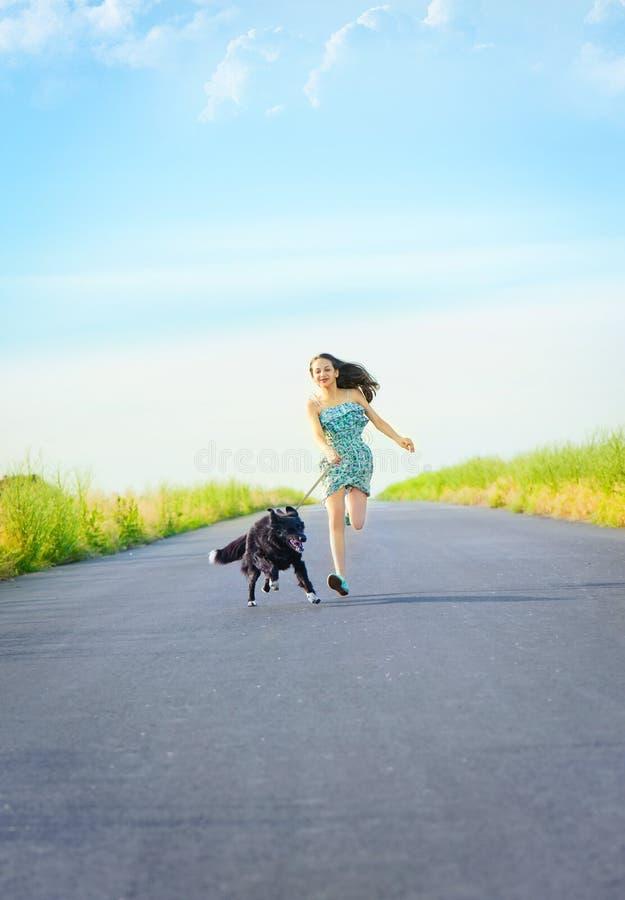 Flicka med en hund för en gå arkivfoto