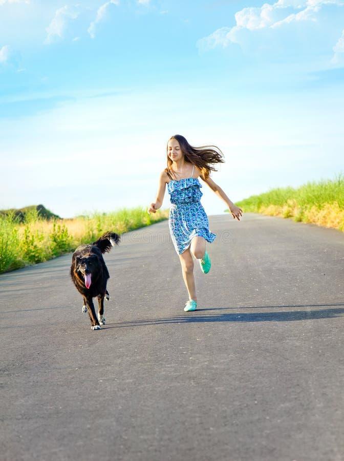 Flicka med en hund för en gå arkivbild