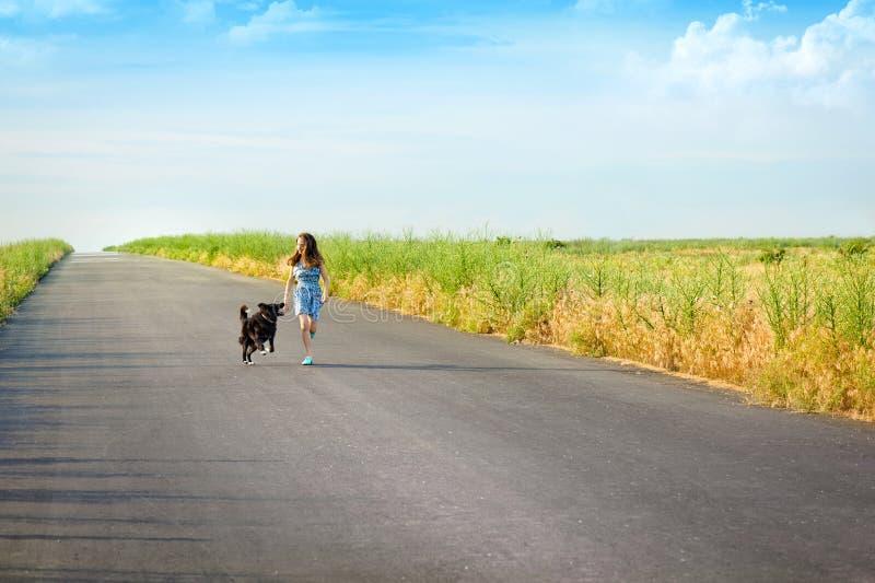 Flicka med en hund för en gå arkivfoton