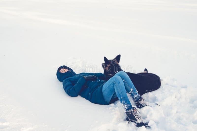 Flicka med en hund på kusten av en vintersjö arkivfoton