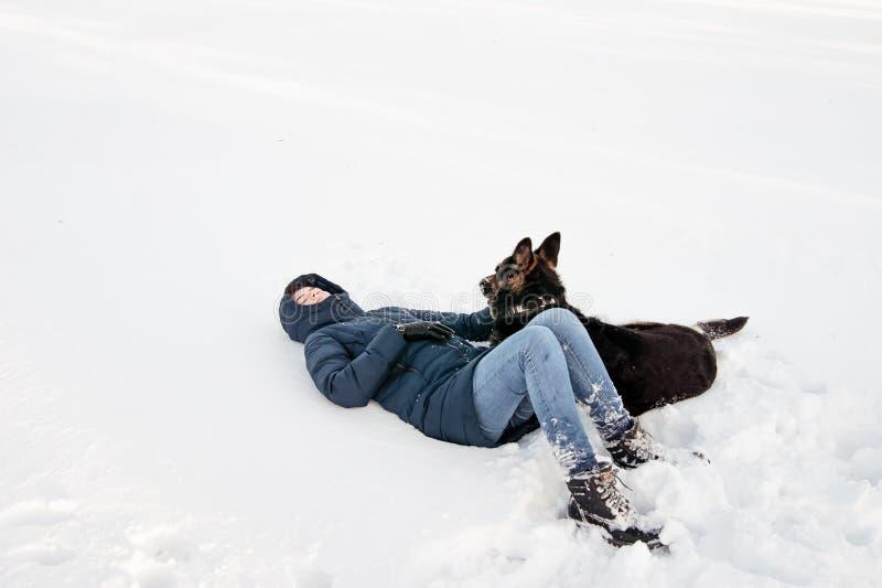 Flicka med en hund på kusten av en vintersjö arkivbild