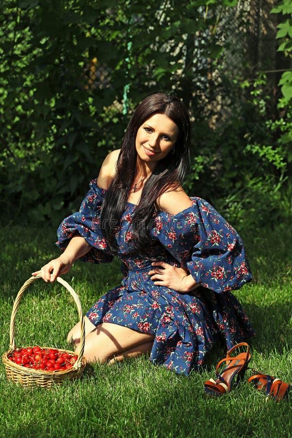 Flicka med en korg av körsbär royaltyfri bild