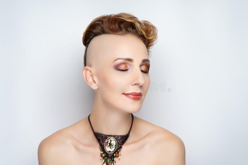 Flicka med en kort frisyr och en rakad tempel arkivbild