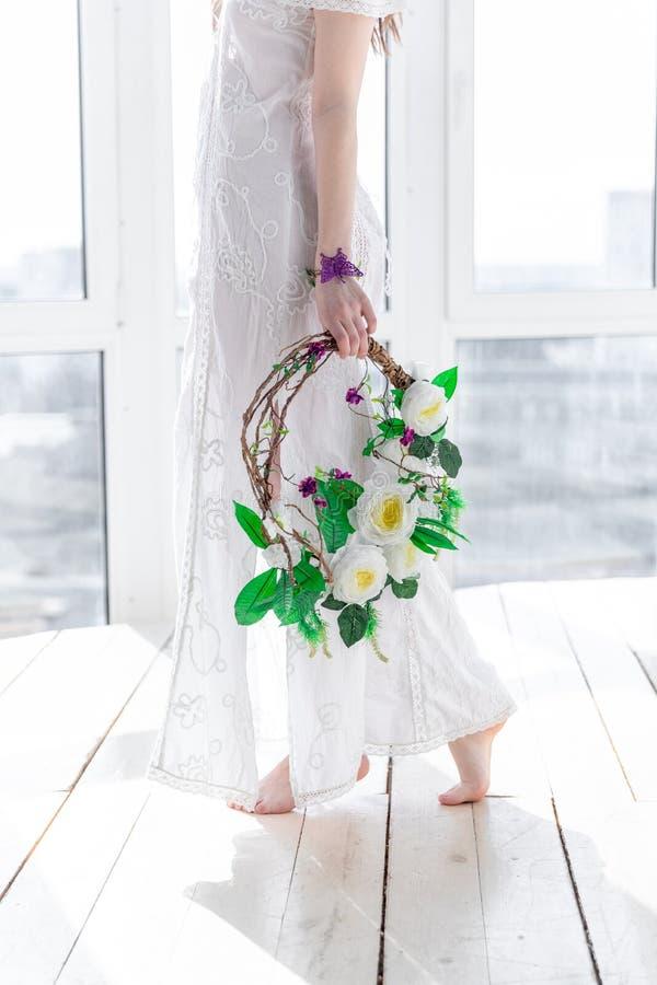 Flicka med en krans av blommor i hög tangent royaltyfri bild