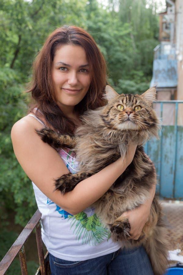 Flicka med en Maine Coon katt arkivbild