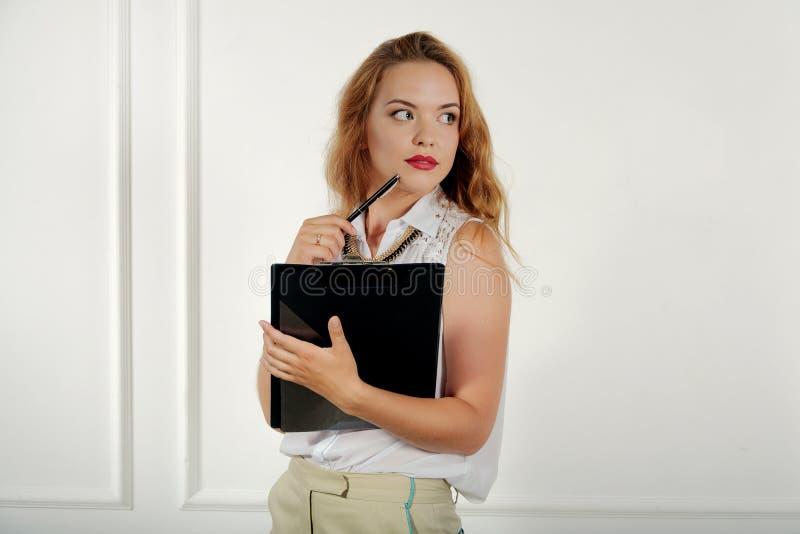 Flicka med en mapp i hennes hand som bort hänsynsfullt ser arkivbild